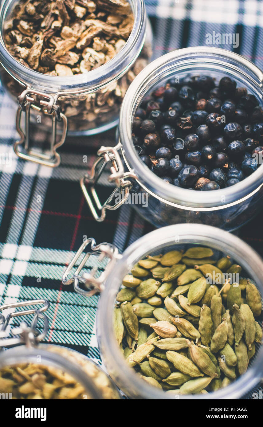Whisky and Gin Ingredients: in glass jar on blue and white tartan - Stock Image