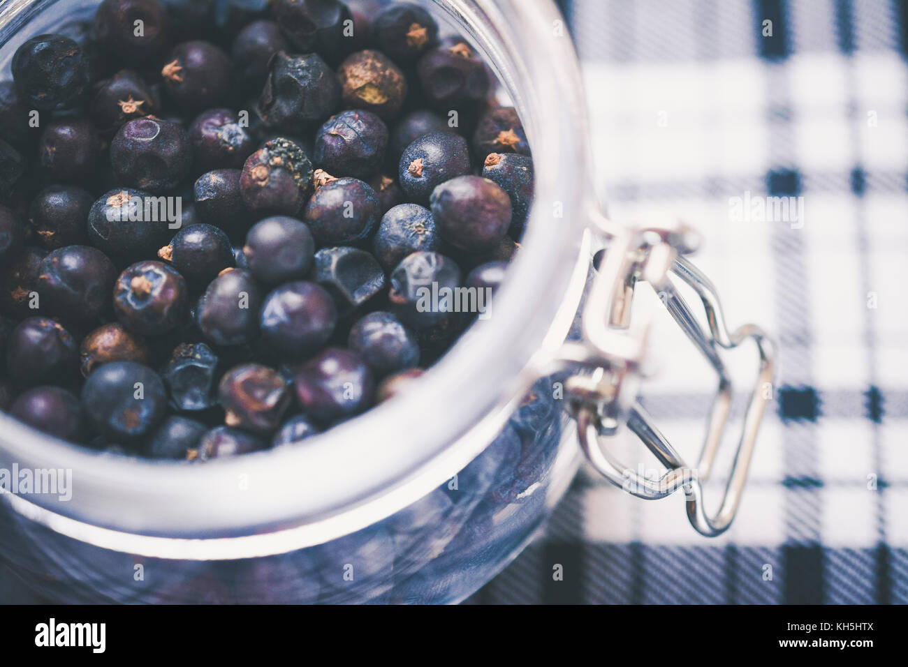 Gin Ingredient: juniper berries in glass jar on blue and white tartan - Stock Image
