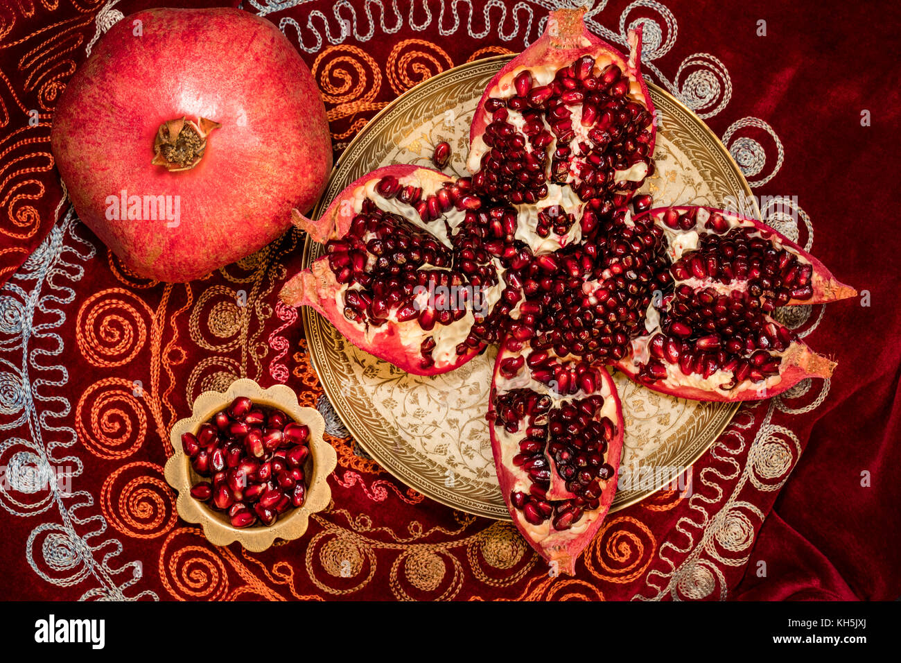 Top view of peeled pomegranate and ruby grains in a bowl on  oriental tablecloth - Stock Image