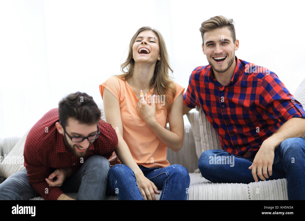 group of young people laughing and sitting on the couch - Stock Image