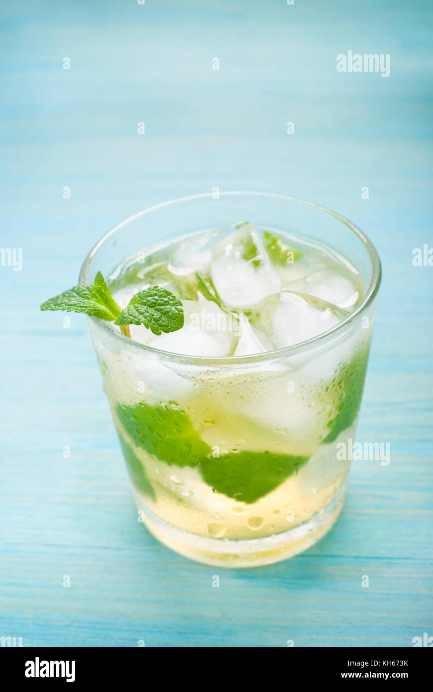 cocktail with mint and ice on blue wooden background - Stock Image