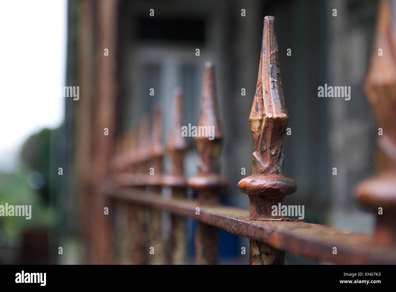 Rusty old Victorian fence railing with shallow depth of field and leading line into the distance - Stock Image