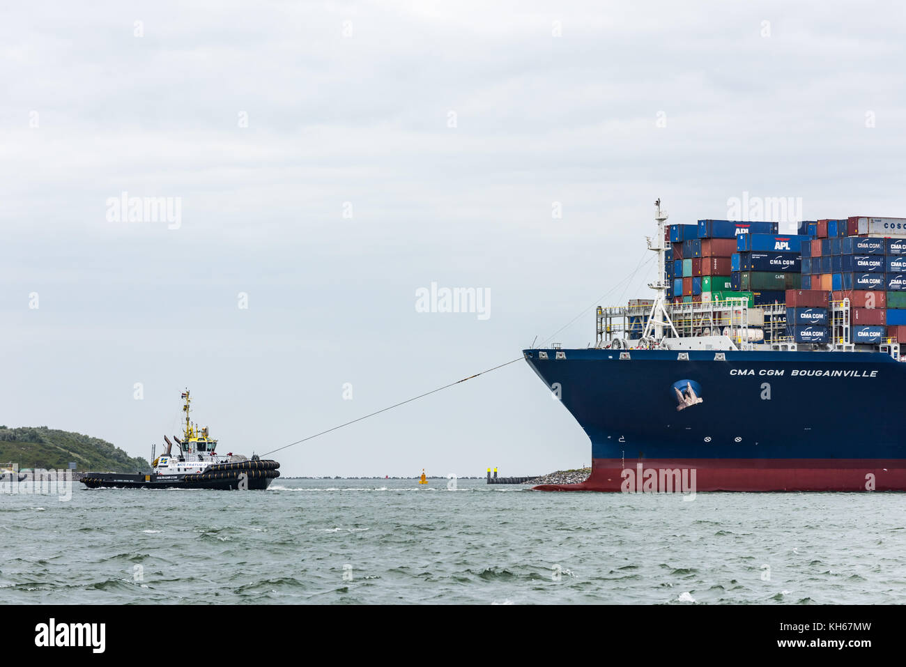 ROTTERDAM, THE NETHERLANDS - JUNE 12, 2017: A tug boat brings the ultra large container ship CMA CGM Bougainville - Stock Image
