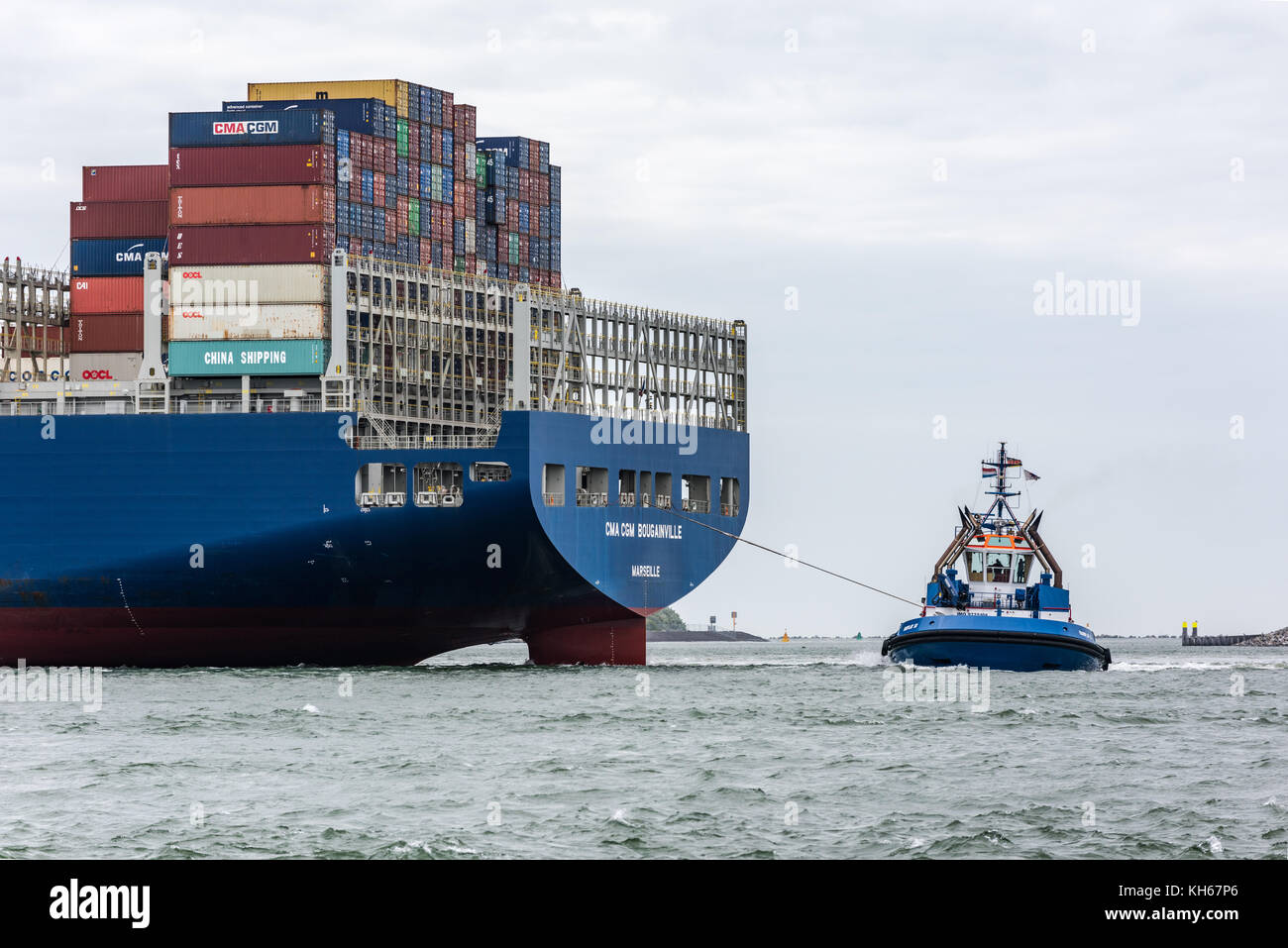 ROTTERDAM, THE NETHERLANDS - JUNE 12, 2017: A tug boat brings the ultra large container ship CMA CGM Bougainville Stock Photo