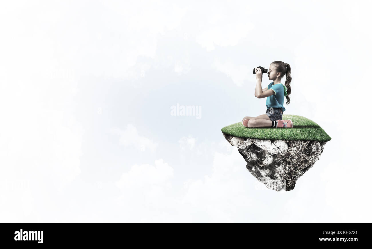 Concept of careless happy childhood with girl looking in binocul - Stock Image