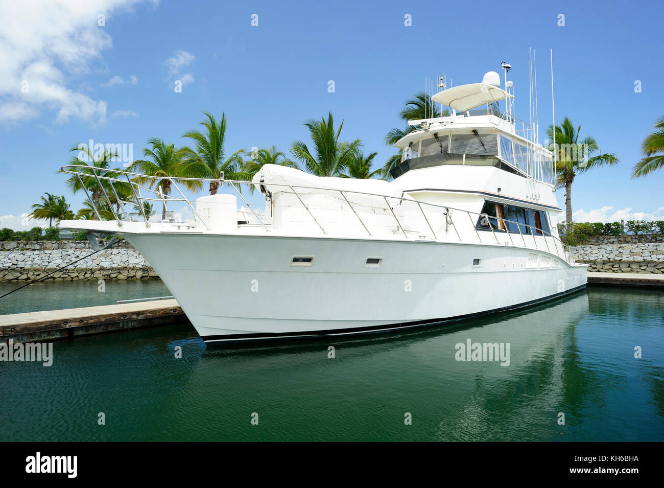 Yacht boat in dock is a large white boat sitting in its dock . - Stock Image