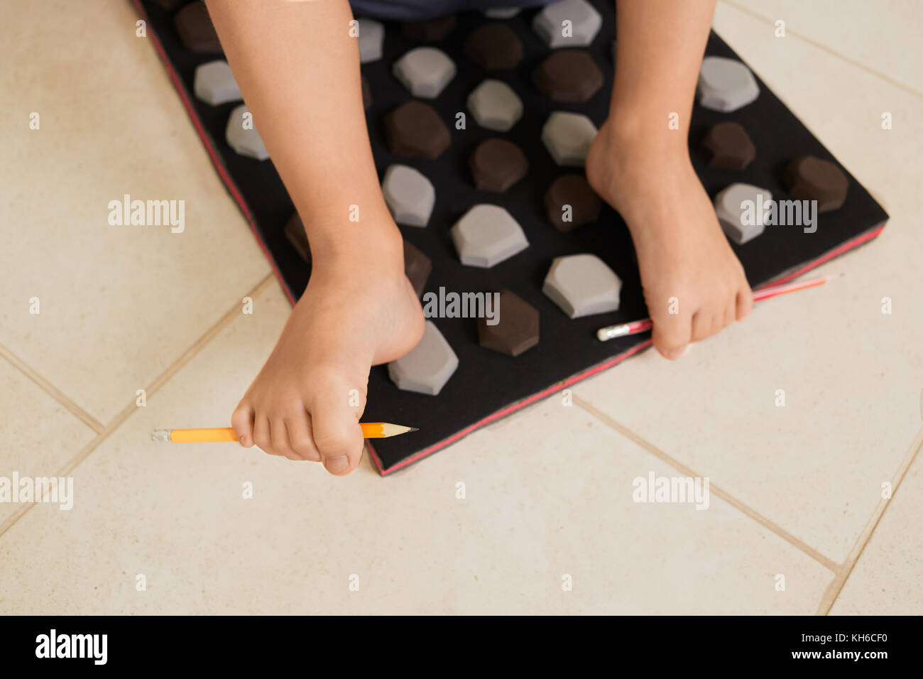 Little boy on massage mat doing exercises for flatfoot prevention.Child flatfoot treatment using special massage - Stock Image