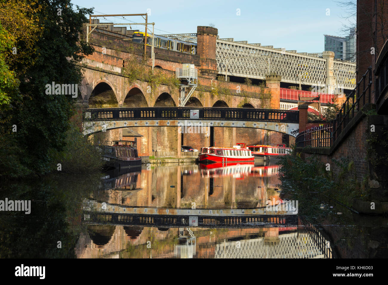 A footbridge, Victorian railway viaducts and canal boats reflected in the Bridgewater Canal at Castlefield, Manchester, England, UK. Stock Photo