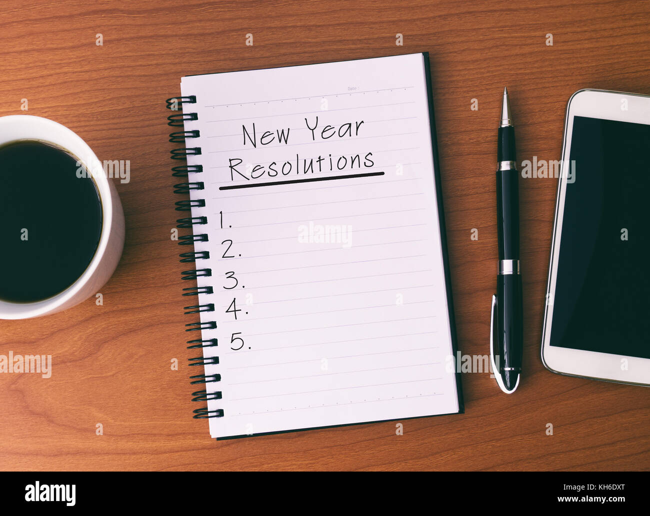 New Year's Resolution List on Notepad, background Coffee, Pen and Smart Phone. - Stock Image
