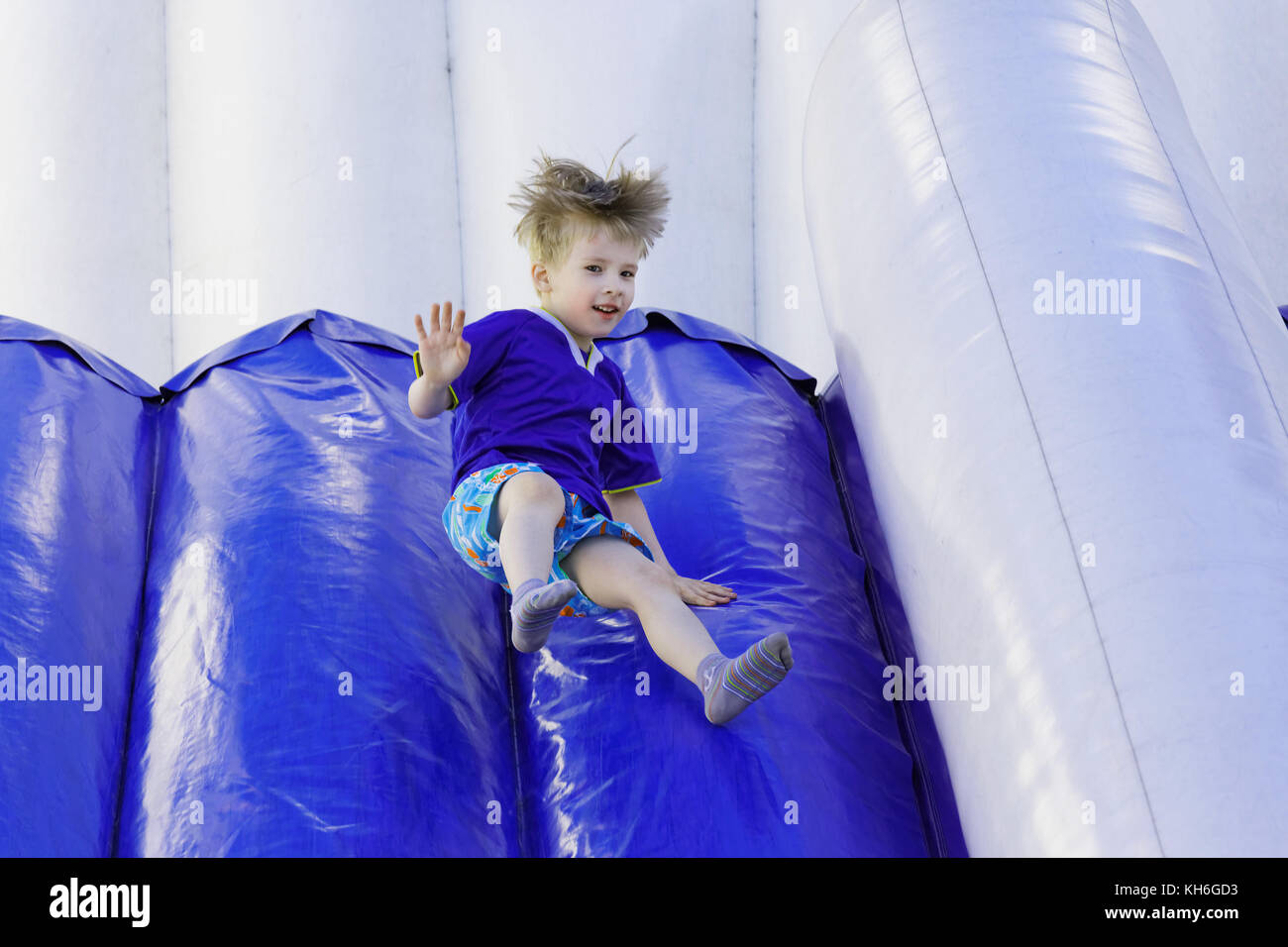 Boy slides down an inflatable slide in the amusement Park - Stock Image