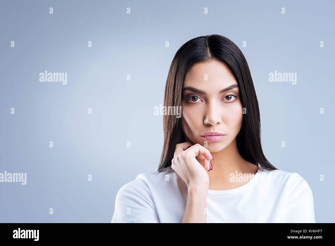 Strict serious mother listening to the teacher at the regular parents meeting - Stock Image