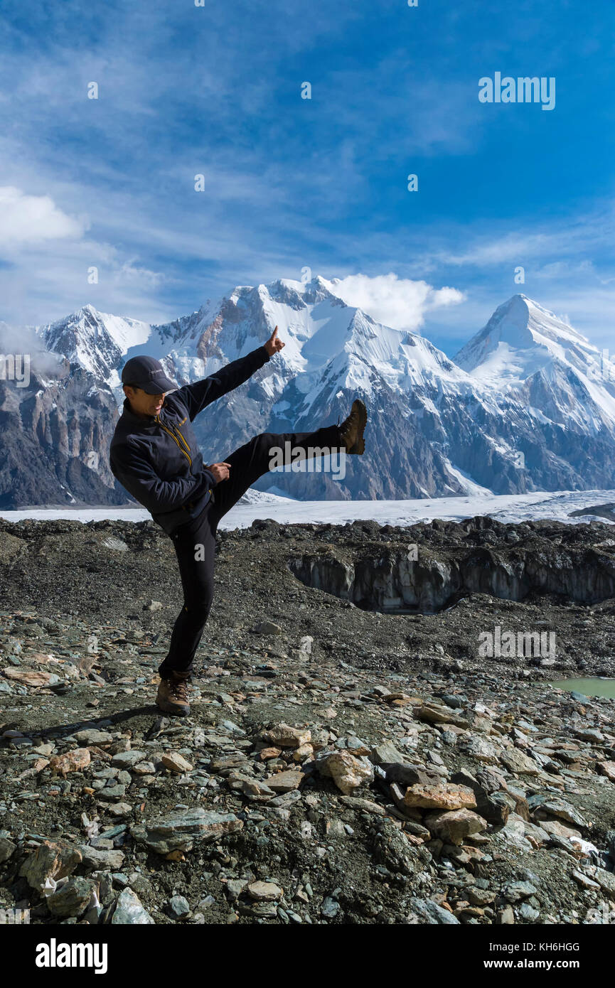 Kyrgyz athlete performing kickboxing in front of Khan Tengri Glacier, Central Tian Shan Mountain range, Border of - Stock Image