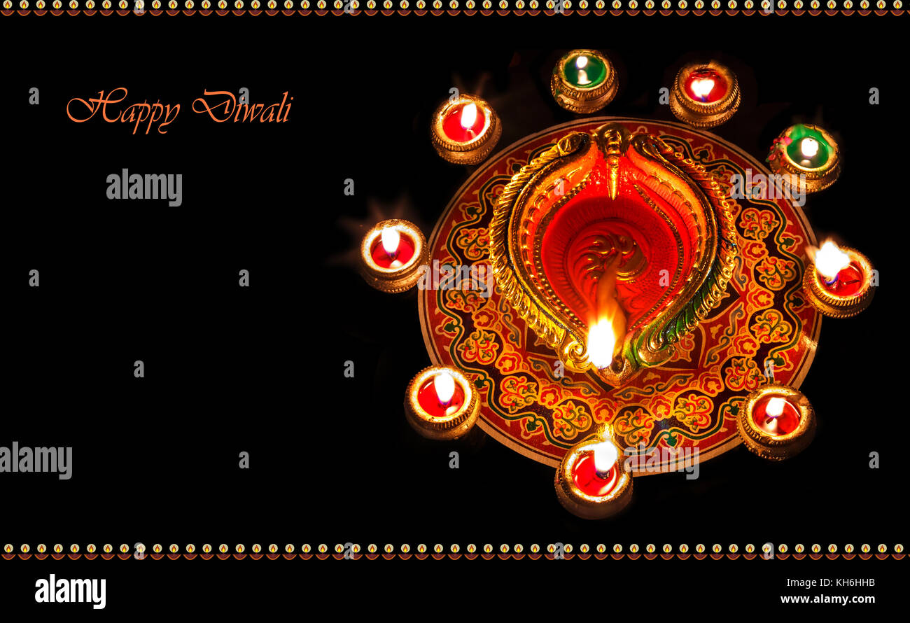 Diwali clay diya lamps with rangoli decorations for festival background content - Stock Image