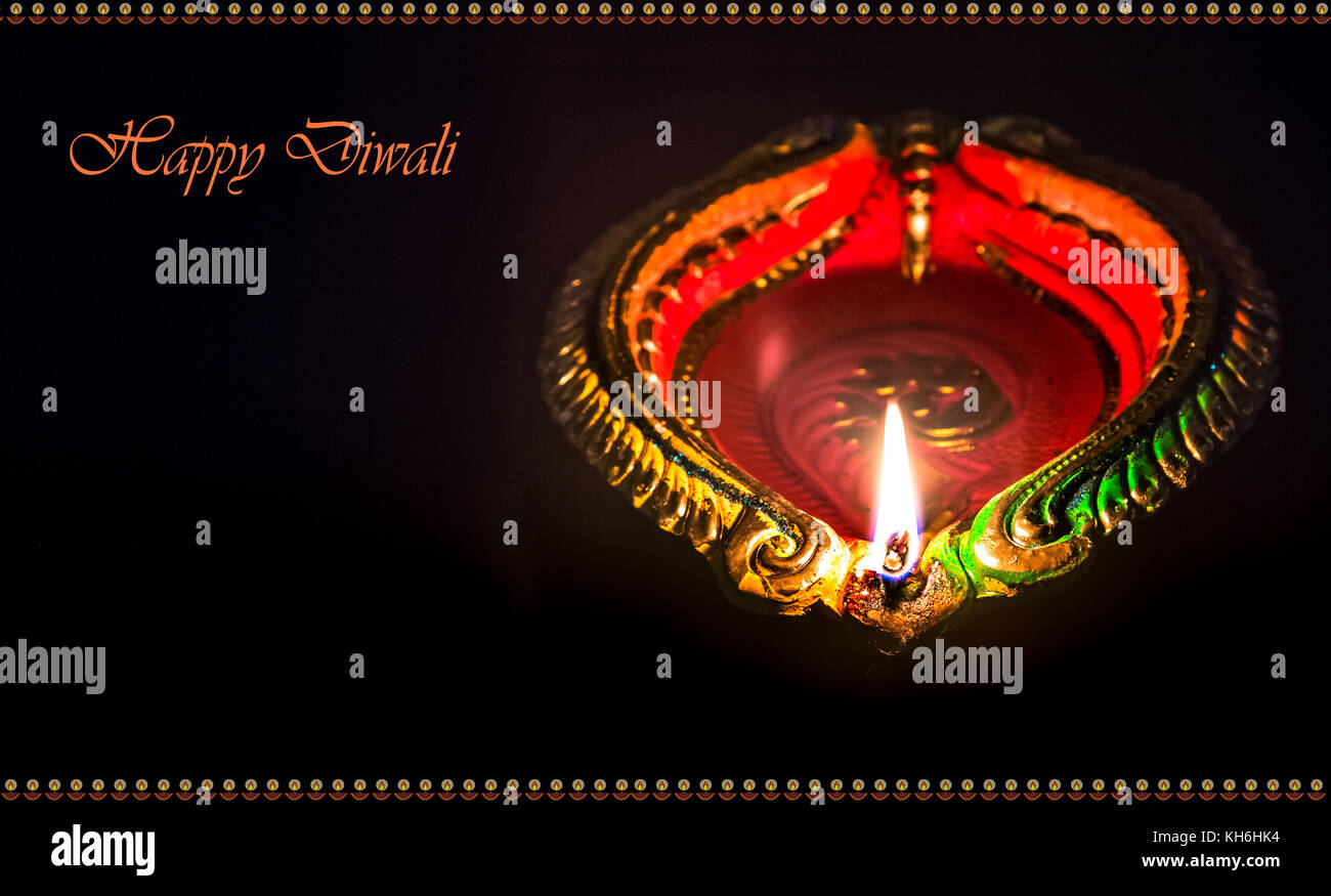 Diwali colorful burning clay diya lamps isolated in dark background with space for greetings content - Stock Image