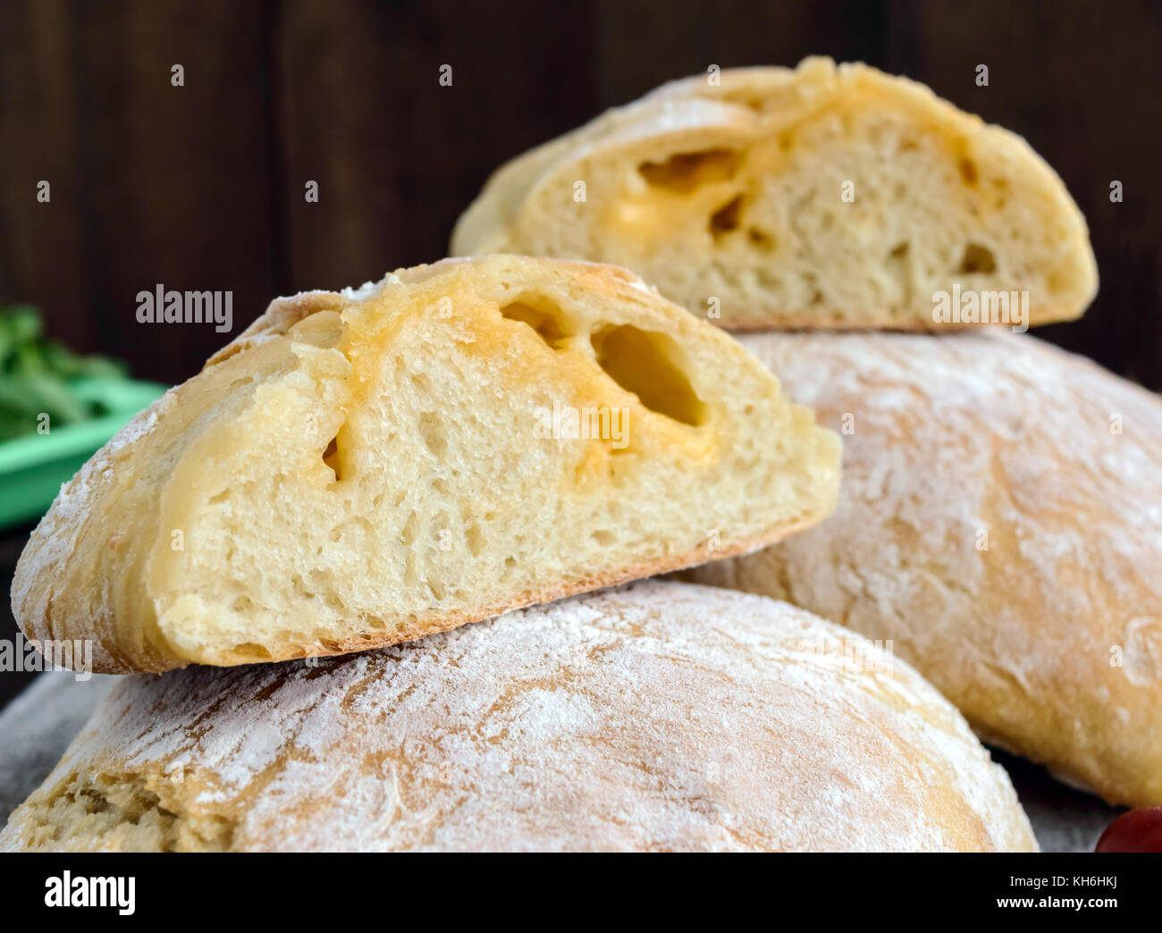 Ciabatta with cheese stuffing - freshly baked Italian white bread on a dark wooden background. For the preparation Stock Photo