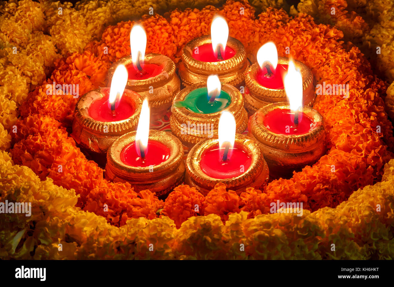 Diwali clay diya lamps with floral decorations in dark background Stock Photo
