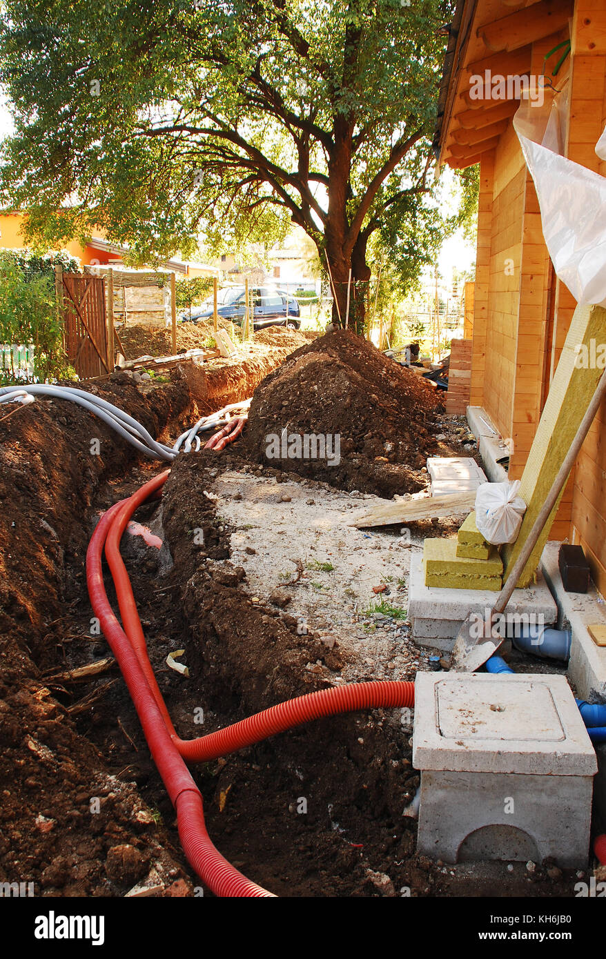 A utilities trench at the side of a newly build wood (fir) house. The trench carries the conduits for gas, water, - Stock Image