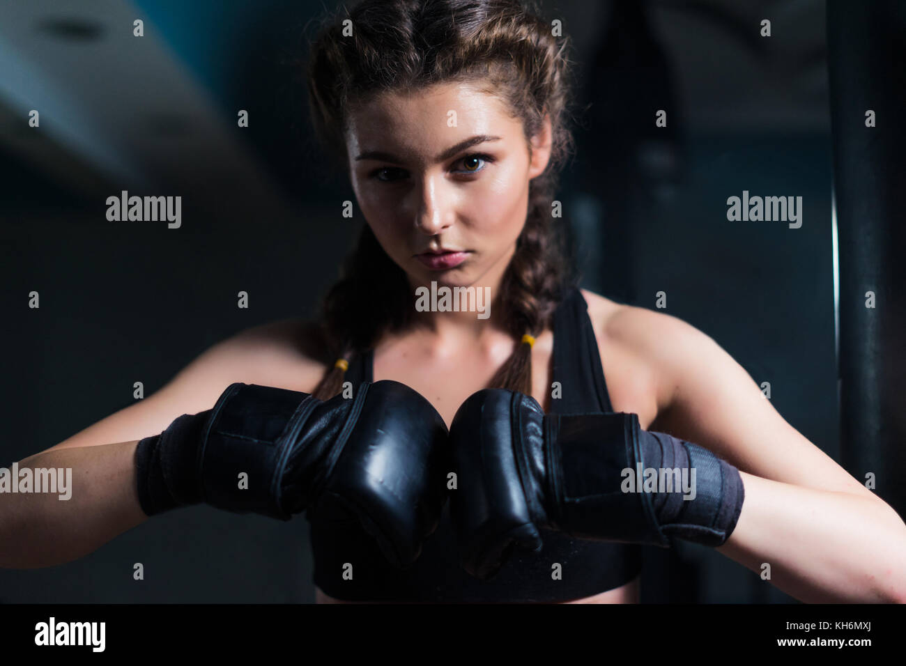 Young fighter boxer girl wearing boxing gloves before  training. - Stock Image