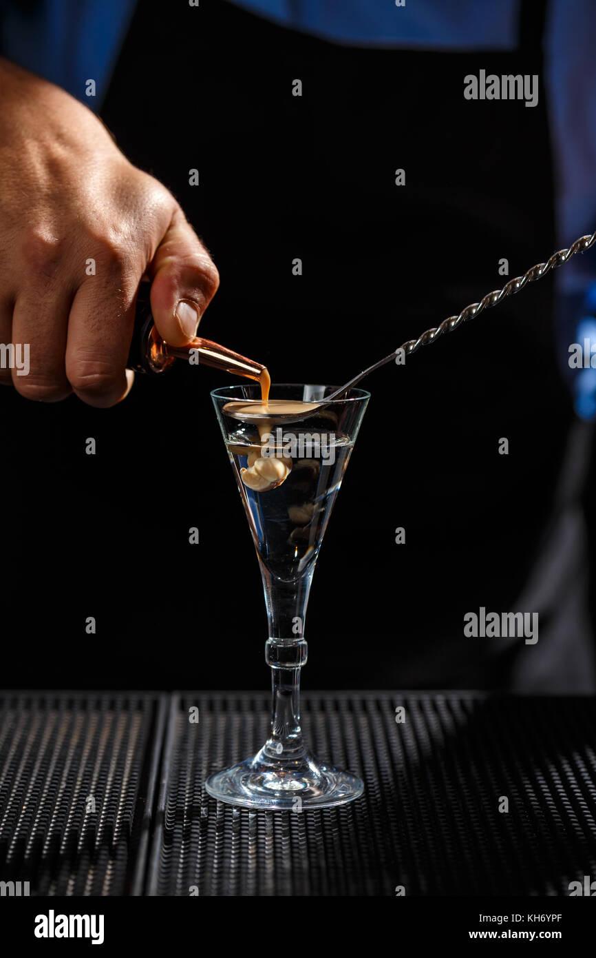 The Bartender makes Brain shot drink - Stock Image