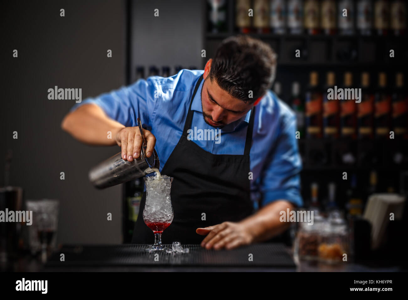 Bartender pouring fresh cocktail in glass - Stock Image