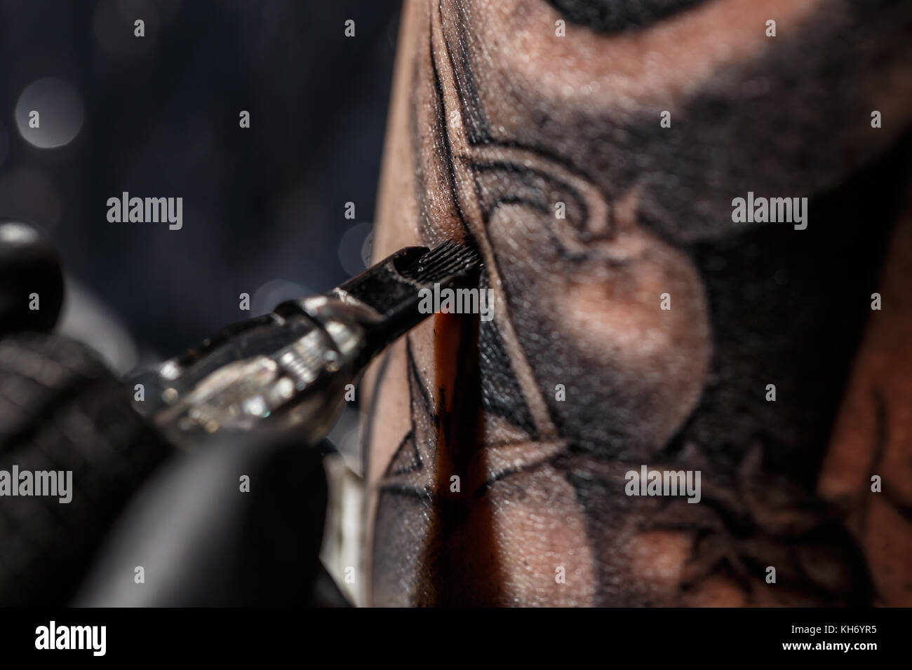 Hands of the artist tattooing of man's skin - Stock Image