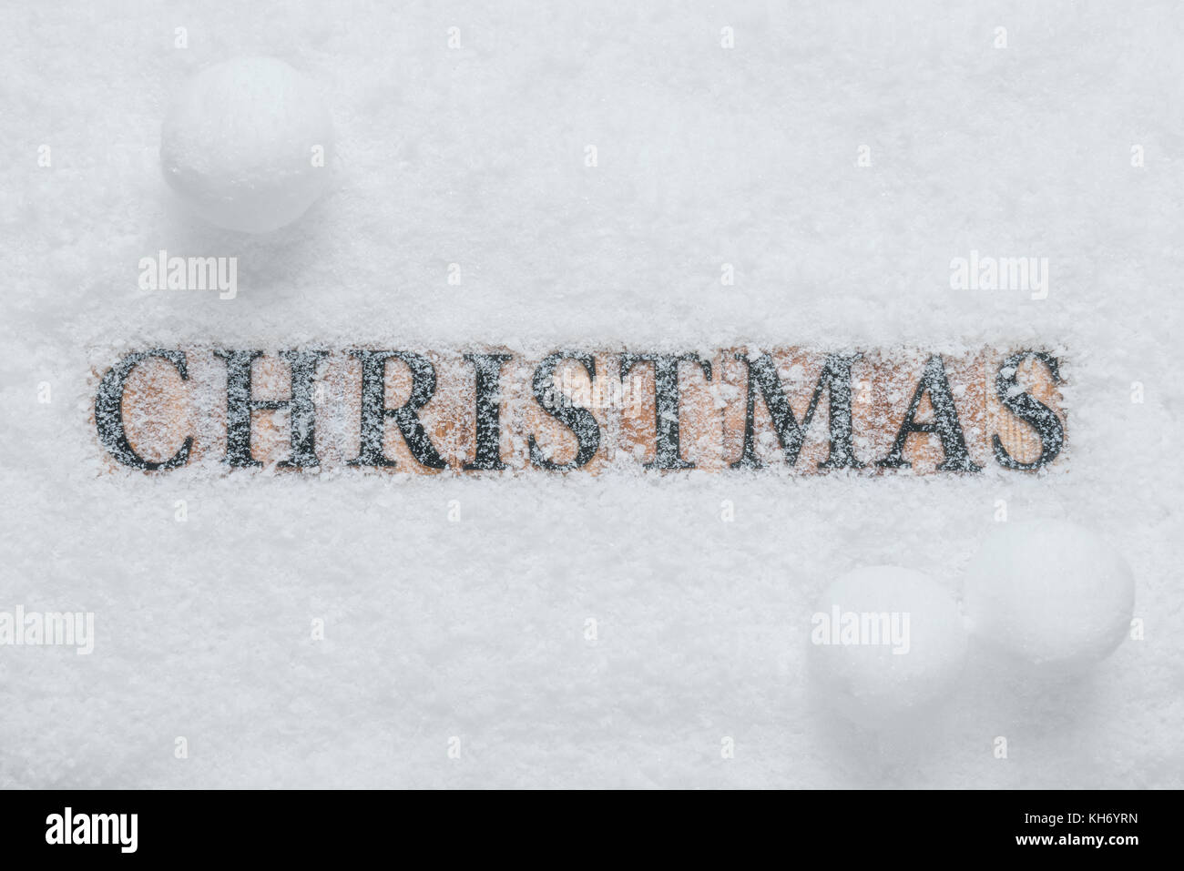 The word Christmas made with wooden letter blocks, on a snow background with snowballs. - Stock Image