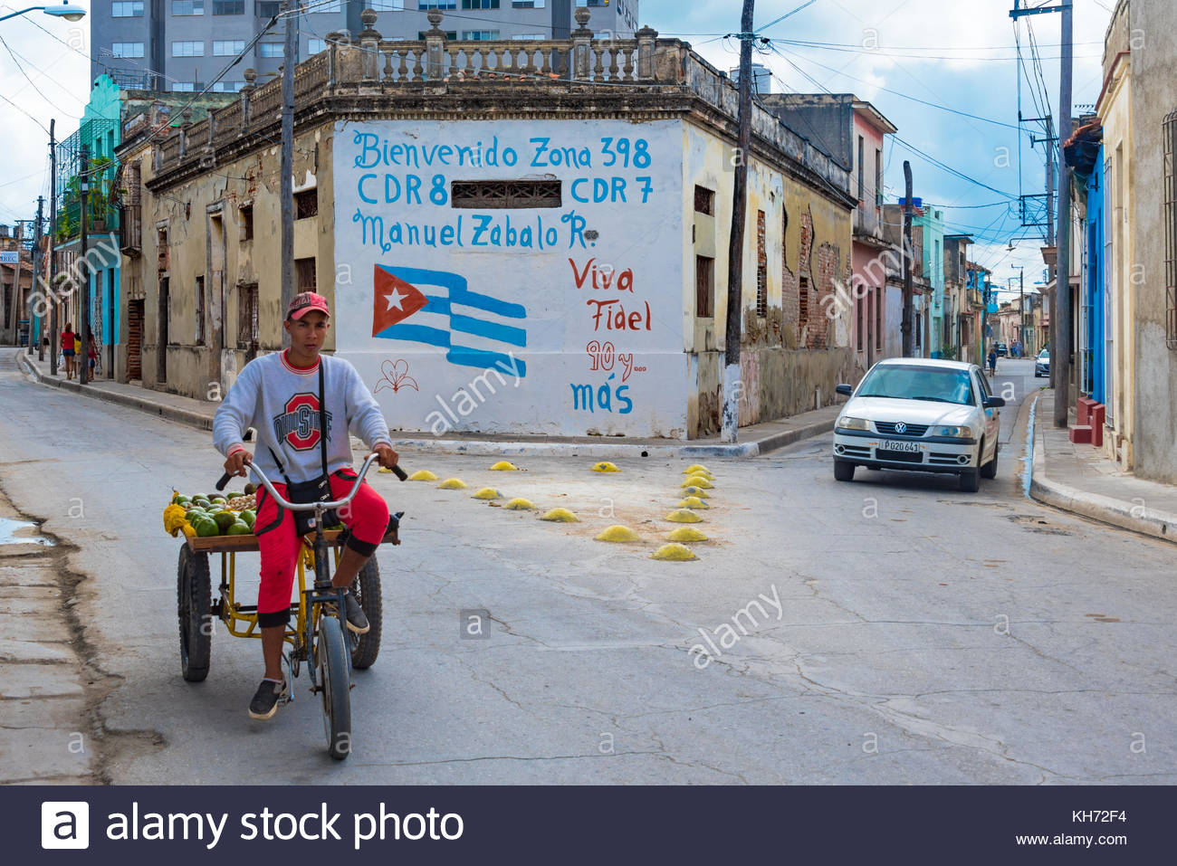 Camaguey, Cuba: Man riding bicitaxi, revolution propaganda as background - Stock Image