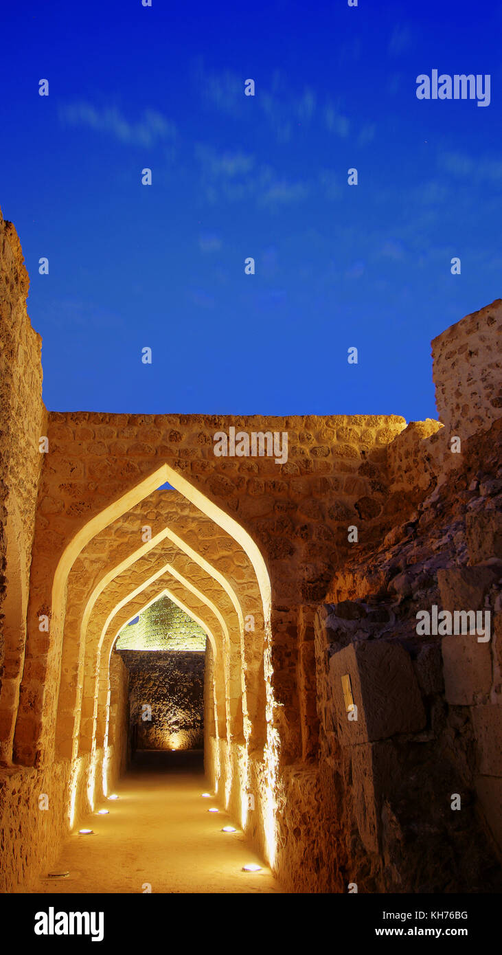 Ruins of Qal'At Al Bahrain, Manama, Bahrain at magical blue hour. a night scape of this UNESCO world Heritage - Stock Image