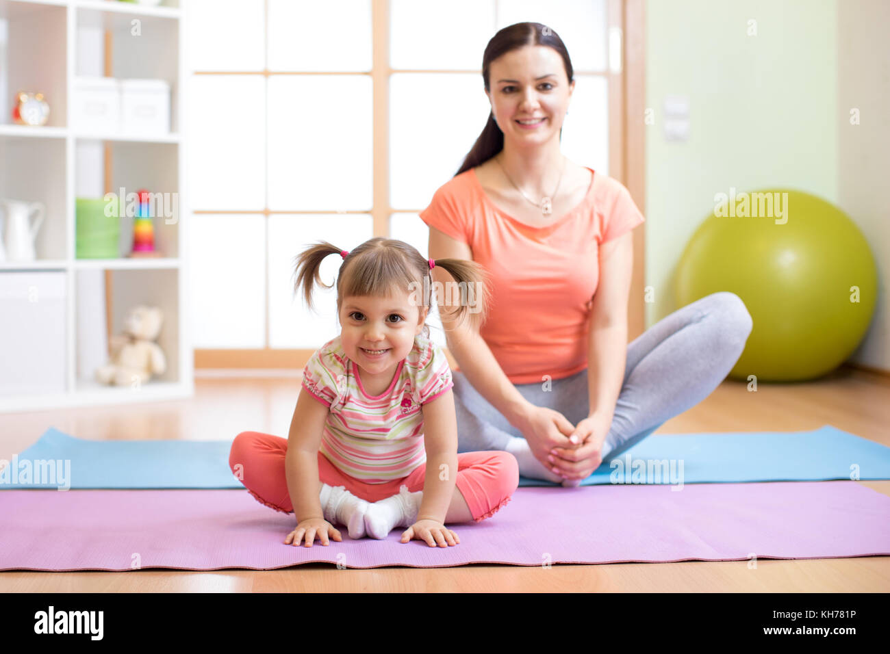 Mother and child daughter practicing yoga together in living room at home. Sport and family concept. - Stock Image