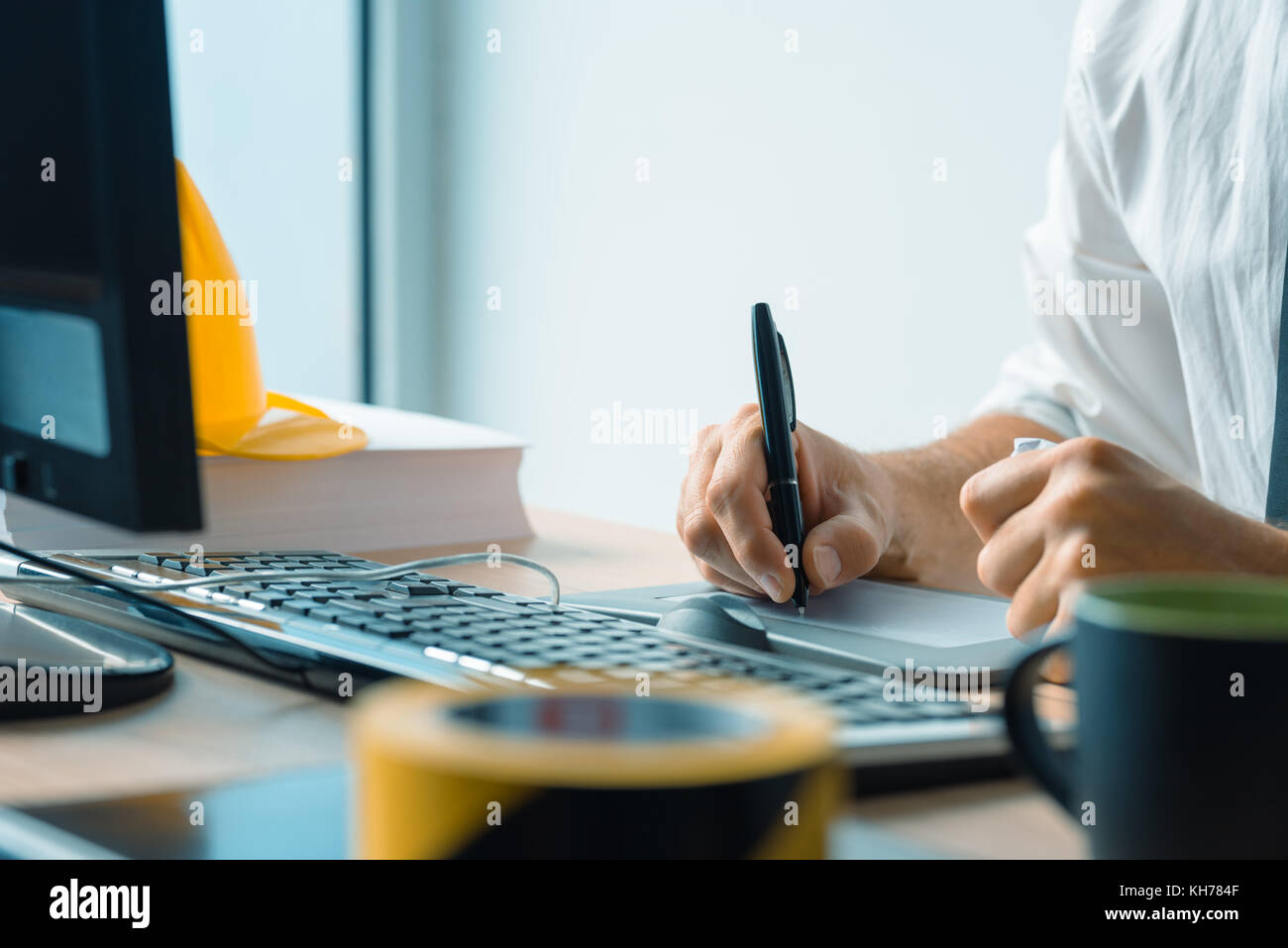 Interior design professional working on graphic tablet sketch pad in architecture studio office - Stock Image