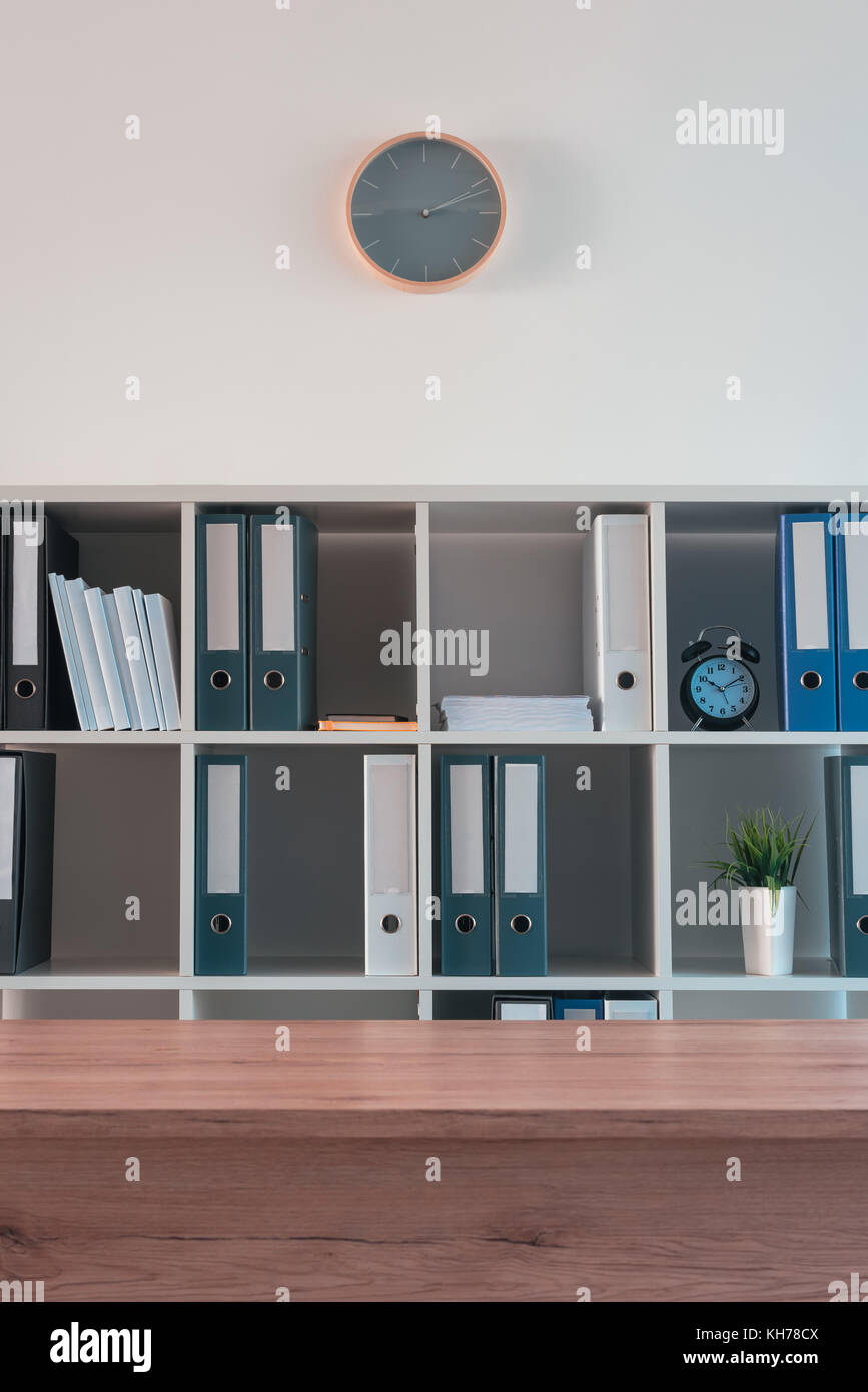 Office shelf with document binders and stationery. Modern workspace interior. - Stock Image