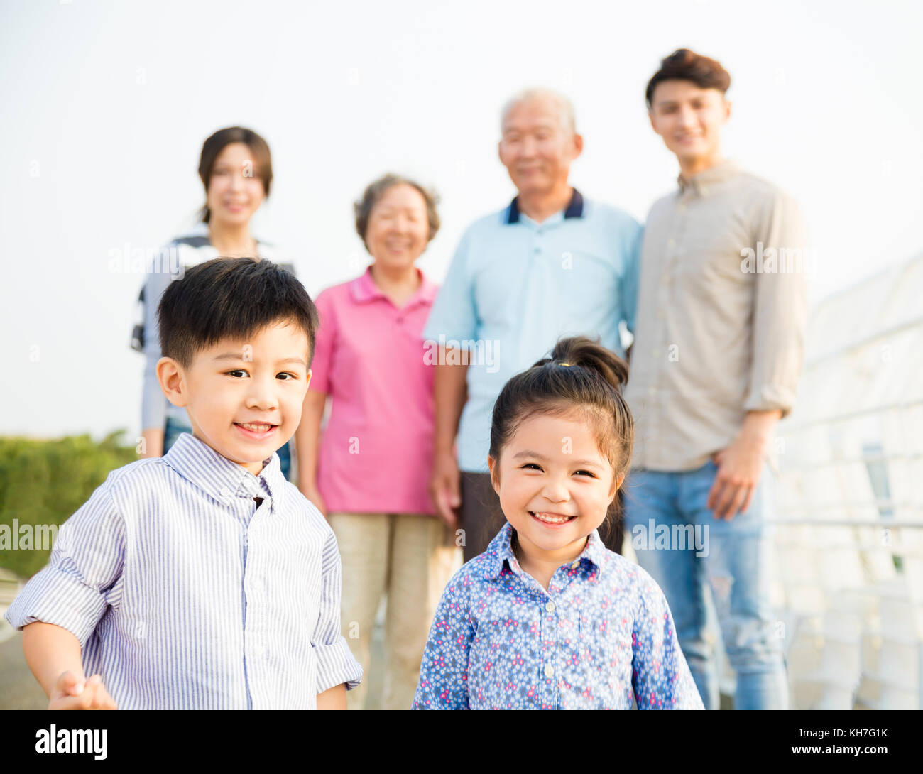 Multi-generation family having fun together outdoors - Stock Image