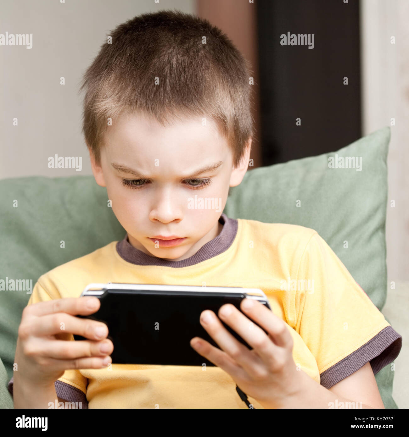 Young boy playing handheld game console Stock Photo