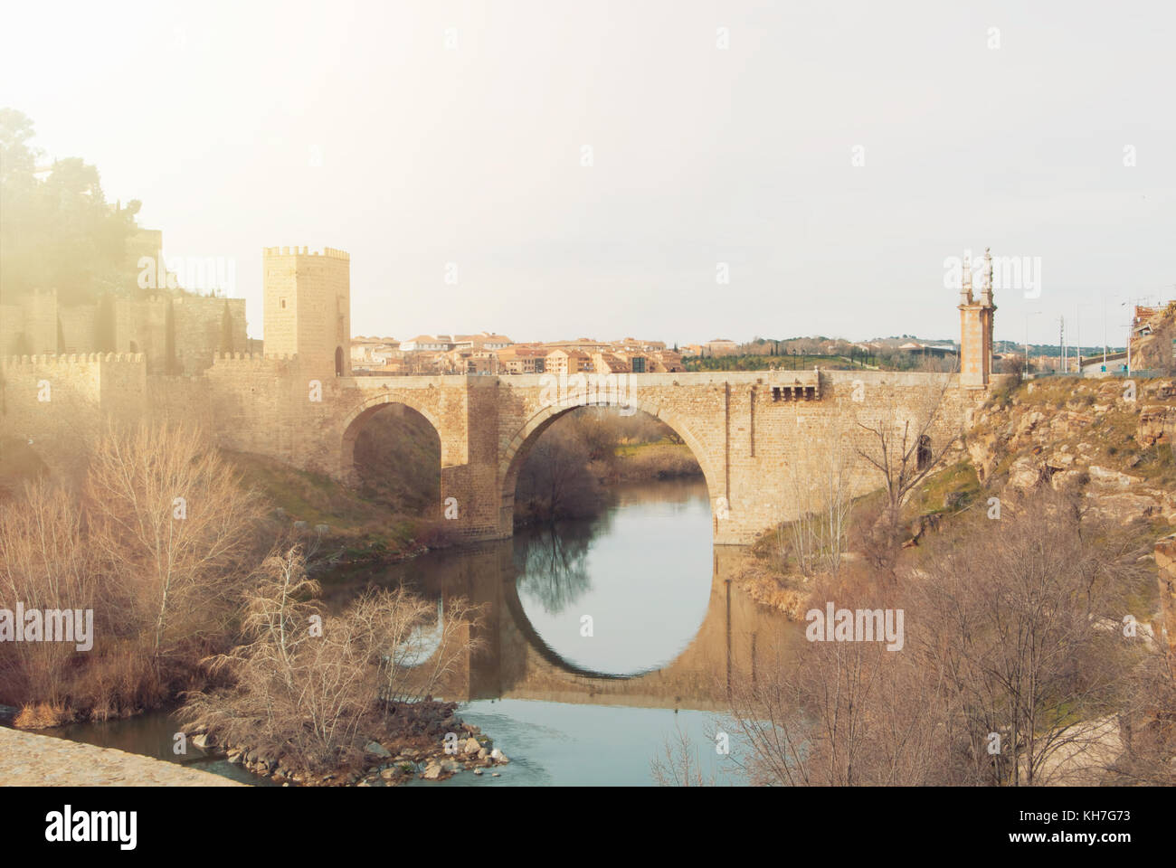 An arch Alcantara Bridge over the Tagus River and its reflection in water on winter evening day, Toledo. - Stock Image