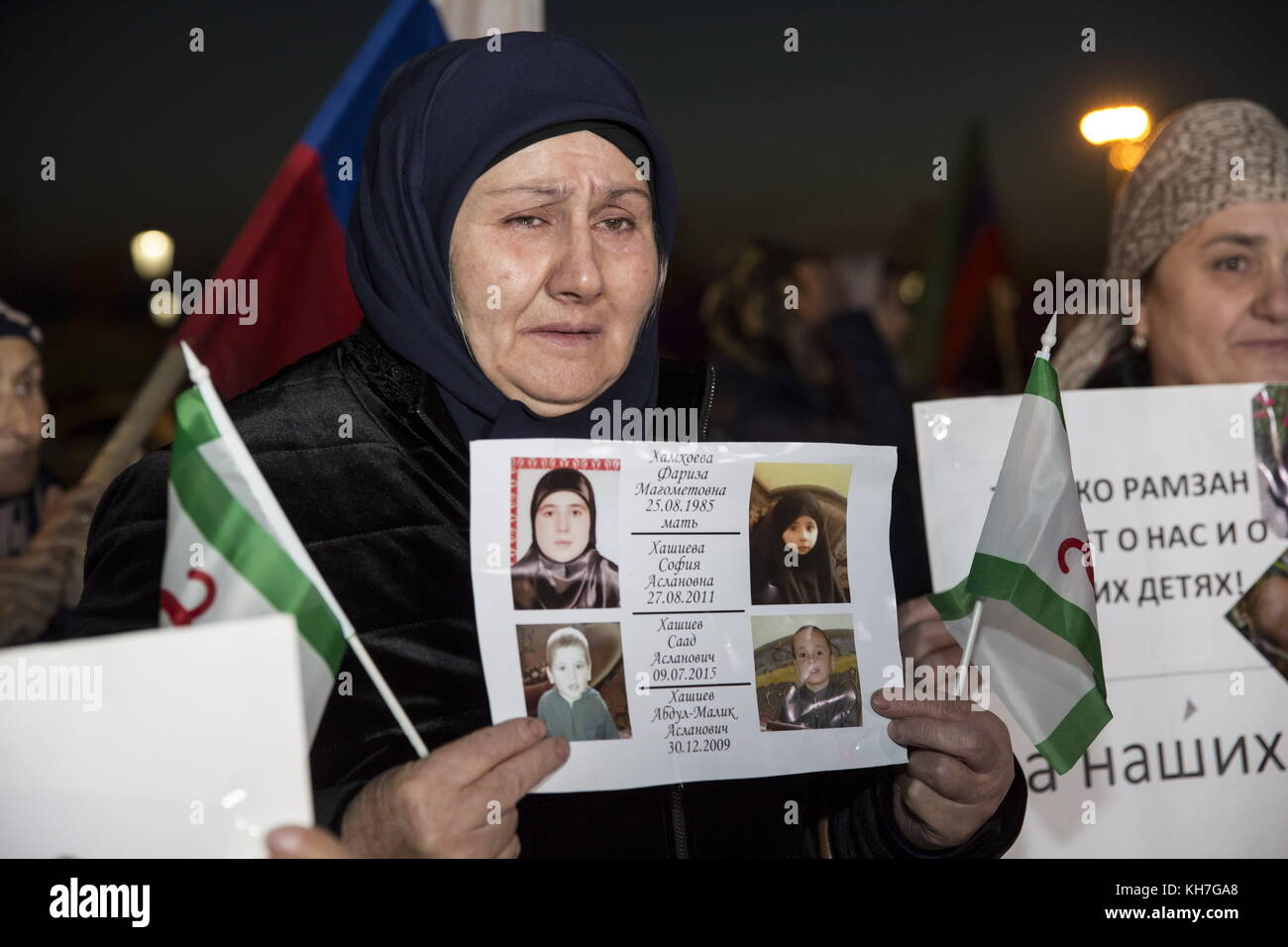Grozny, Russia. 13th Nov, 2017. A woman holds photos of her missing relatives as women and children evacuated from - Stock Image