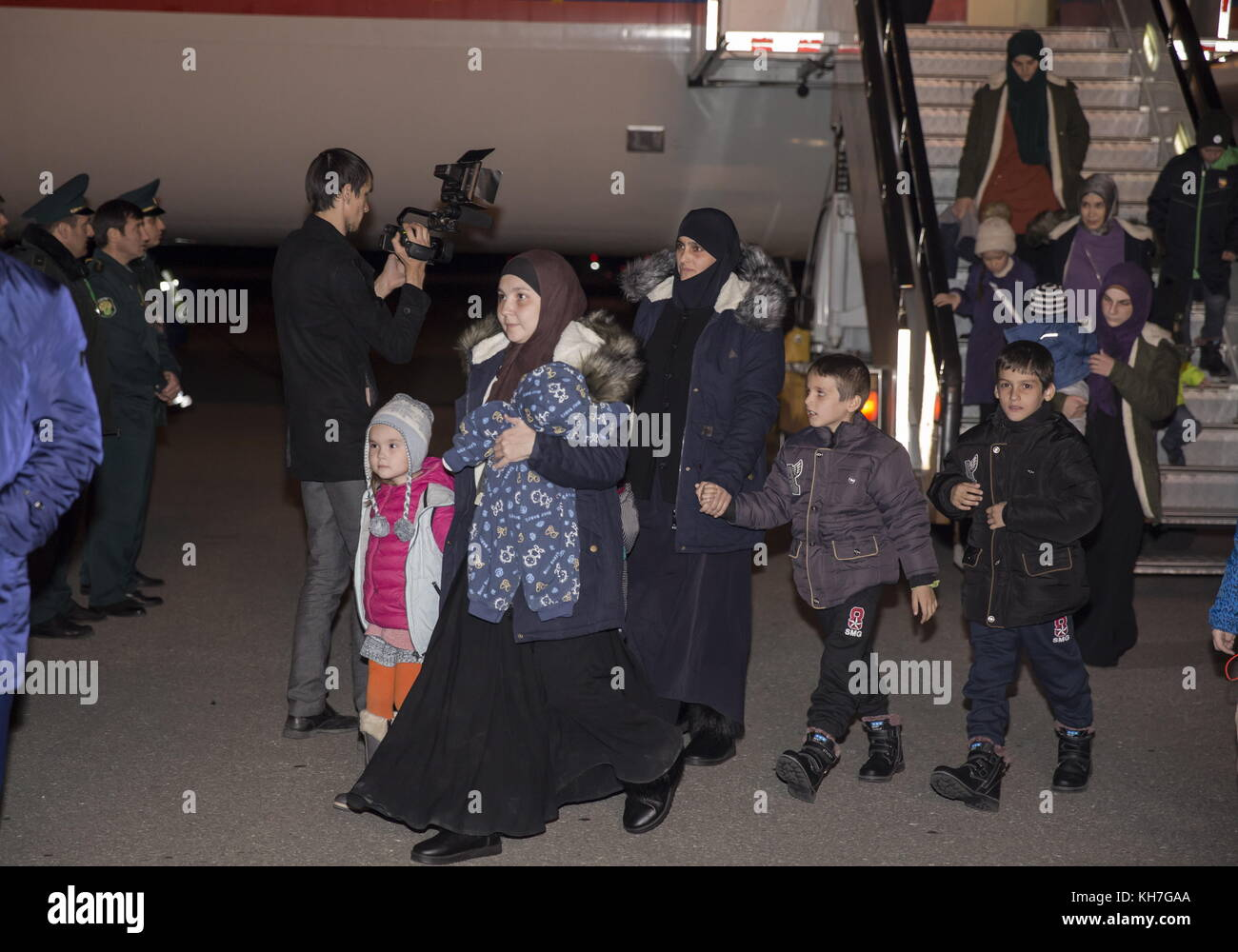 Grozny, Russia. 13th Nov, 2017. Women and children evacuated from Syria leave a plane as they arrive at Grozny Airport. - Stock Image