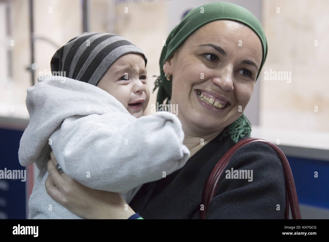 Grozny, Russia. 13th Nov, 2017. A smiling woman holds a baby as women and children evacuated from Syria arrive at - Stock Image