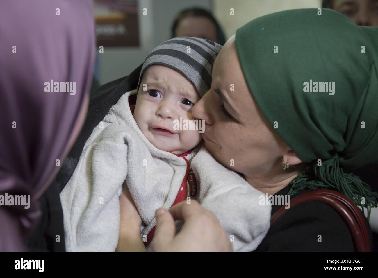 Grozny, Russia. 13th Nov, 2017. A woman kisses a baby as women and children evacuated from Syria arrive at Grozny - Stock Image
