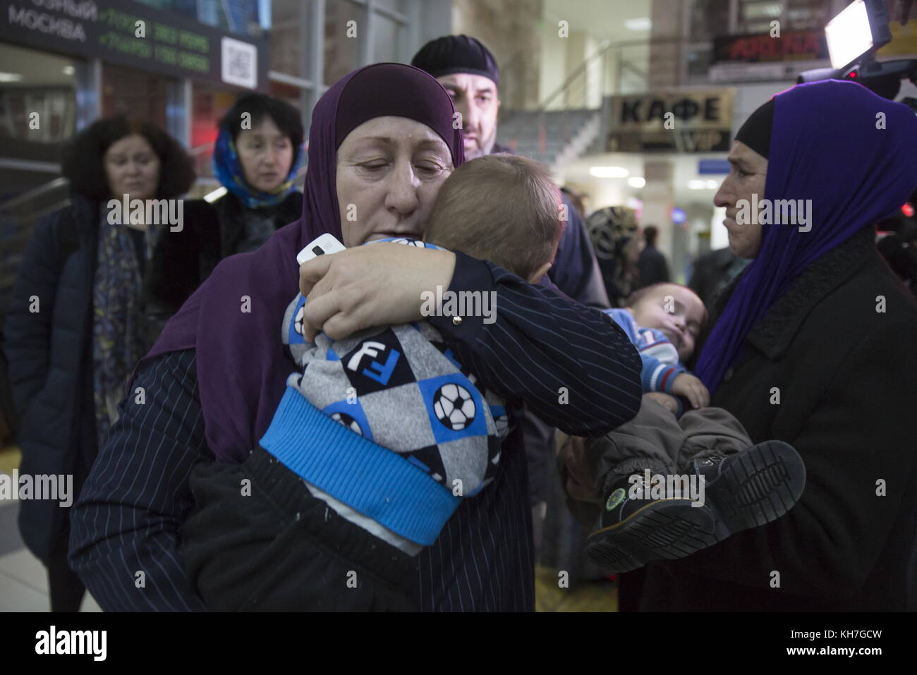 Grozny, Russia. 13th Nov, 2017. A woman holds a baby as women and children evacuated from Syria arrive at Grozny - Stock Image