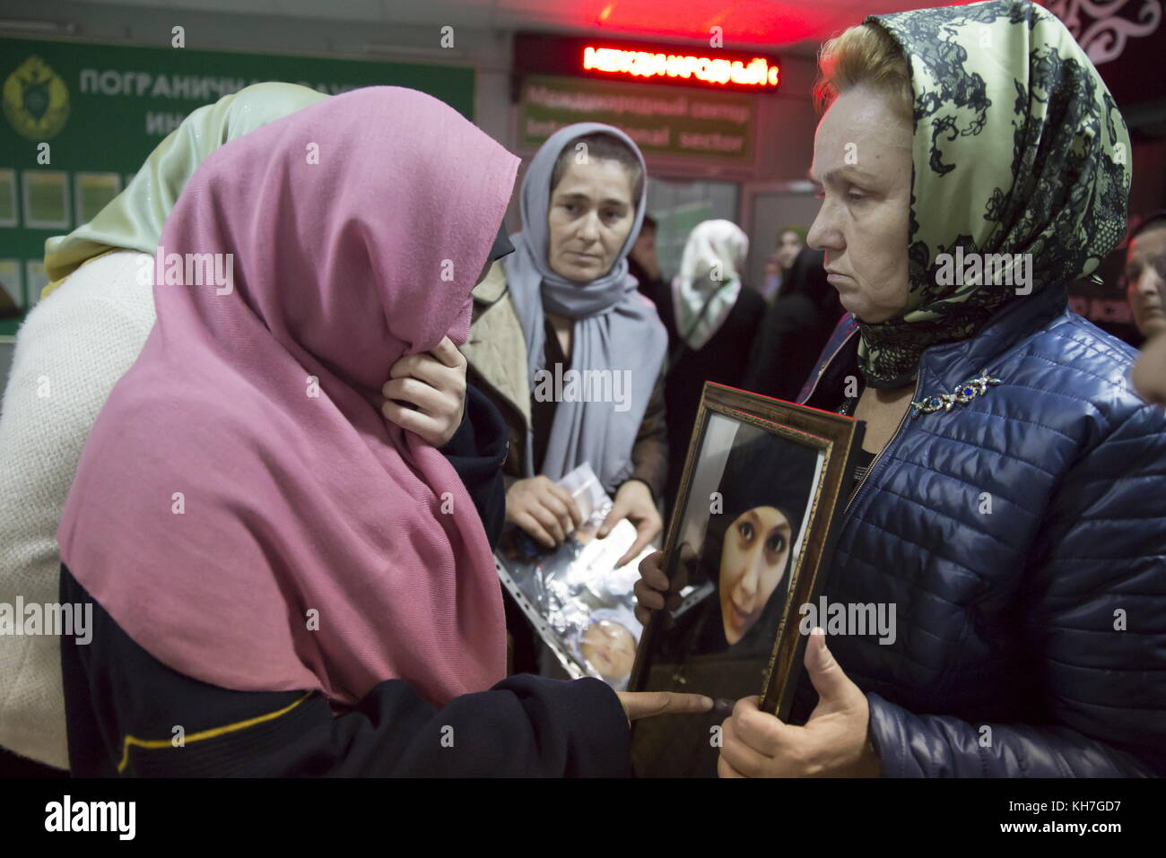 Grozny, Russia. 13th Nov, 2017. A woman holds a photo of her missing relative as women and children evacuated from - Stock Image