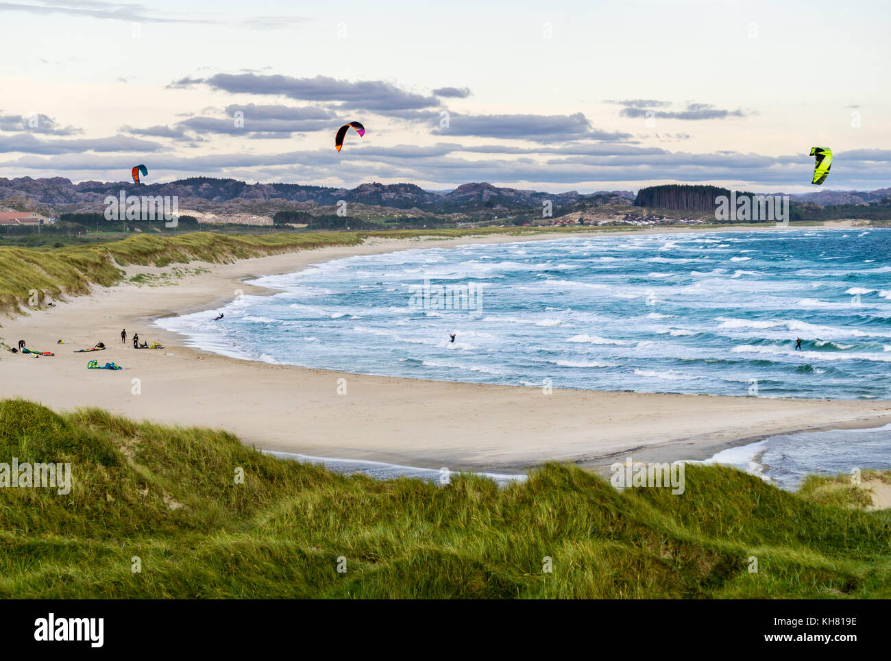 Kitesurfing men in action on stormy sunset evening at Brusand Beach, Norway. - Stock Image