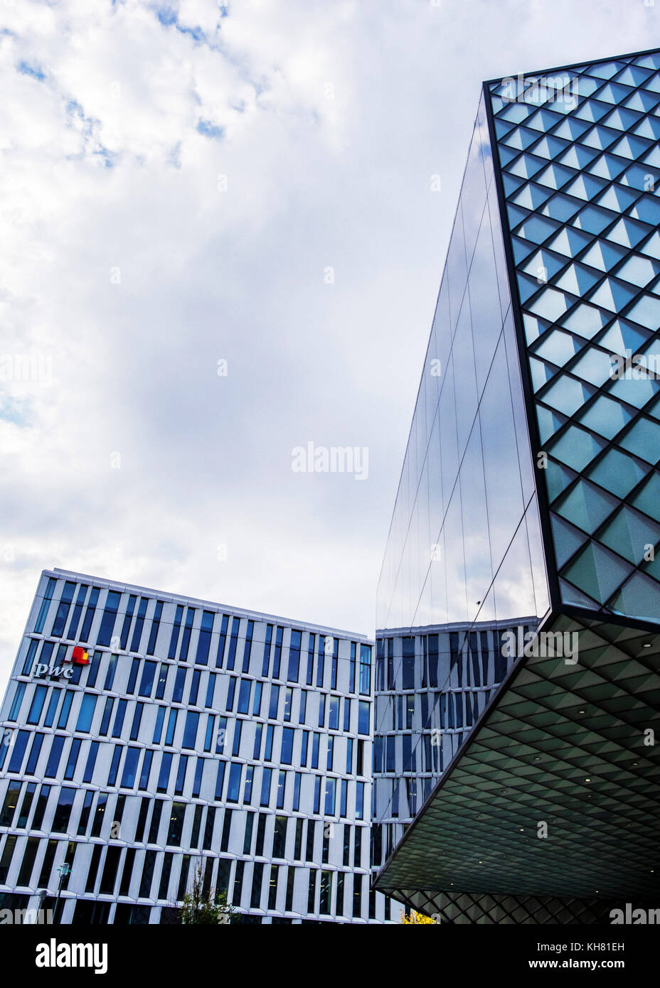 PWC, Price Waterhouse Coopers Accounting and auditing firm. man standing in wiindow of Modern office building, Company - Stock Image