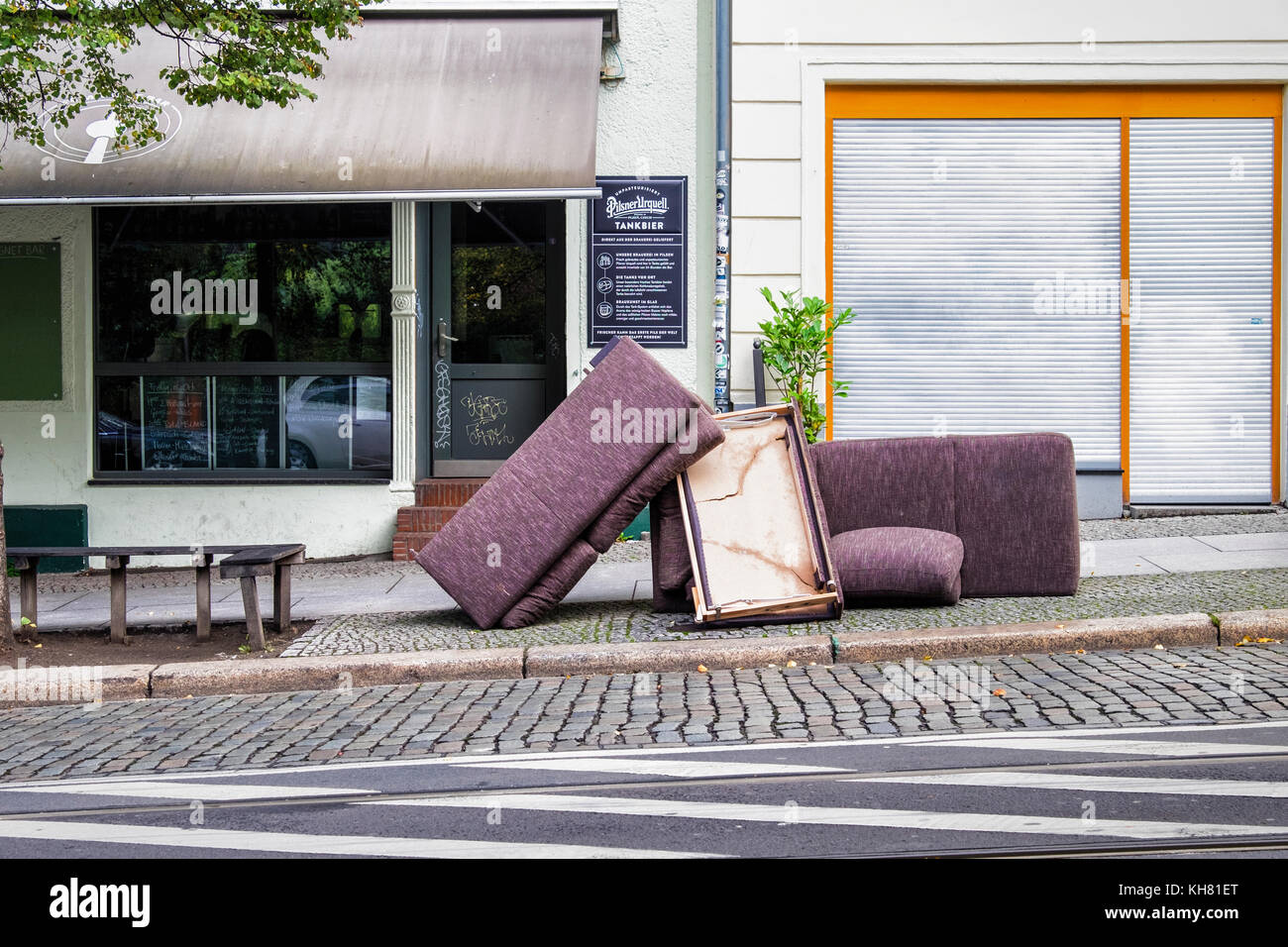 Germnay,Berlin, Abandoned furniture on city pavement outside pub, dumped couches, trashed couch - Stock Image
