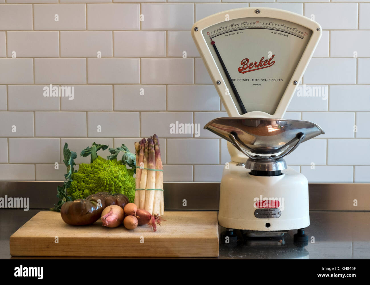 A few choice vegetables wait on a chopping board on a stainless steel kitchen work surface alongside a set of classic - Stock Image