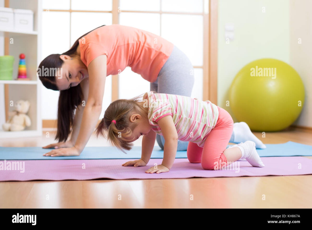 Mother and child daughter practicing yoga together at home. Sport and family concept - Stock Image