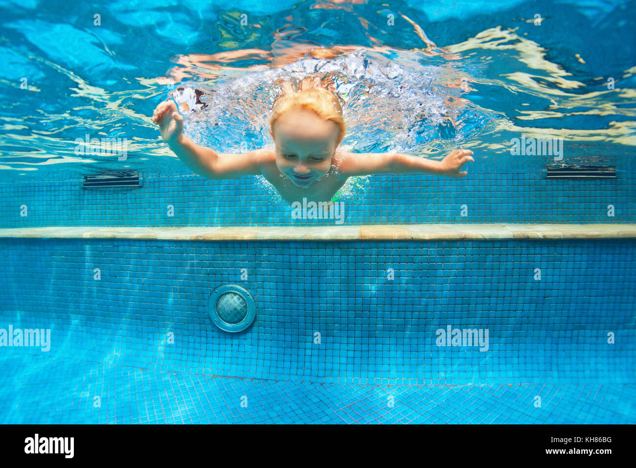 Funny child learn swimming, diving in blue pool with fun - jumping deep down underwater with splashes. Family lifestyle, - Stock Image
