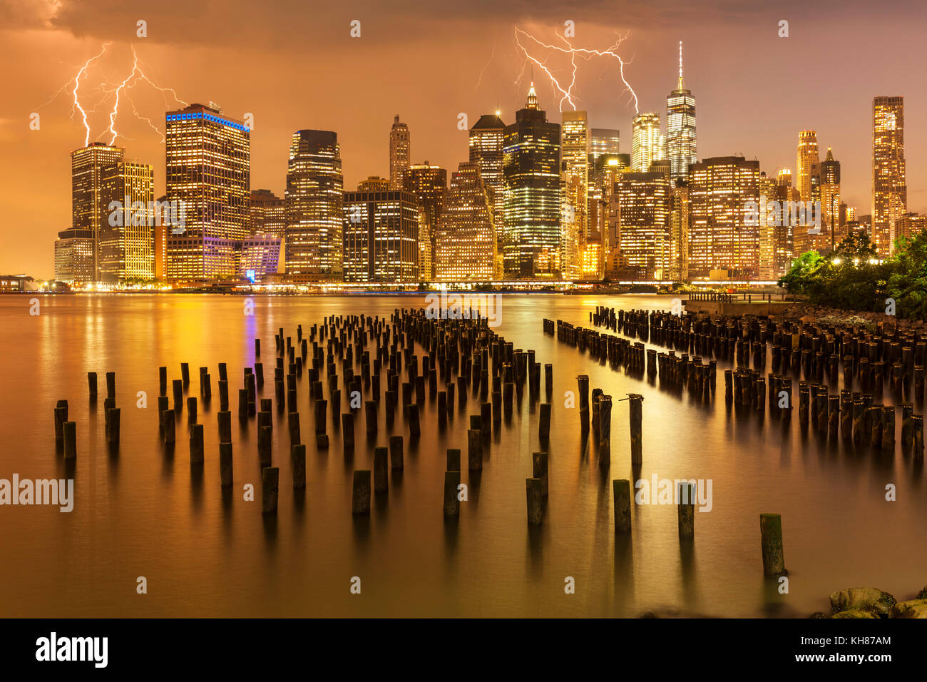 manhattan skyline New York skyline Lightning storm above the skyscrapers with Brooklyn old pier 1 wooden pilings - Stock Image