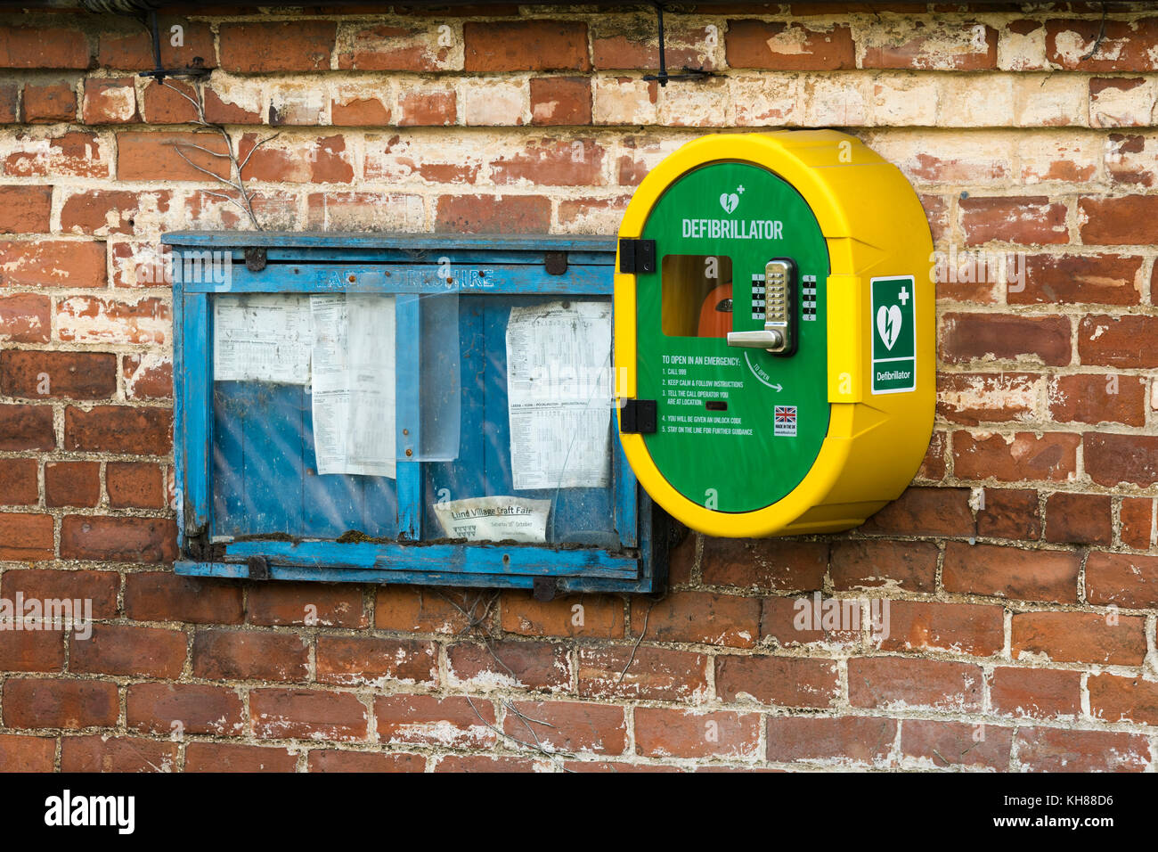 Emergency life saving defibrillator & old village notice board side by side, mounted on external brick wall - Stock Image