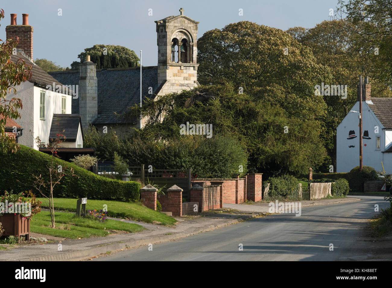 View along quiet, rural country lane towards tall bell tower of St Giles Church & attractive village cottages - Stock Image