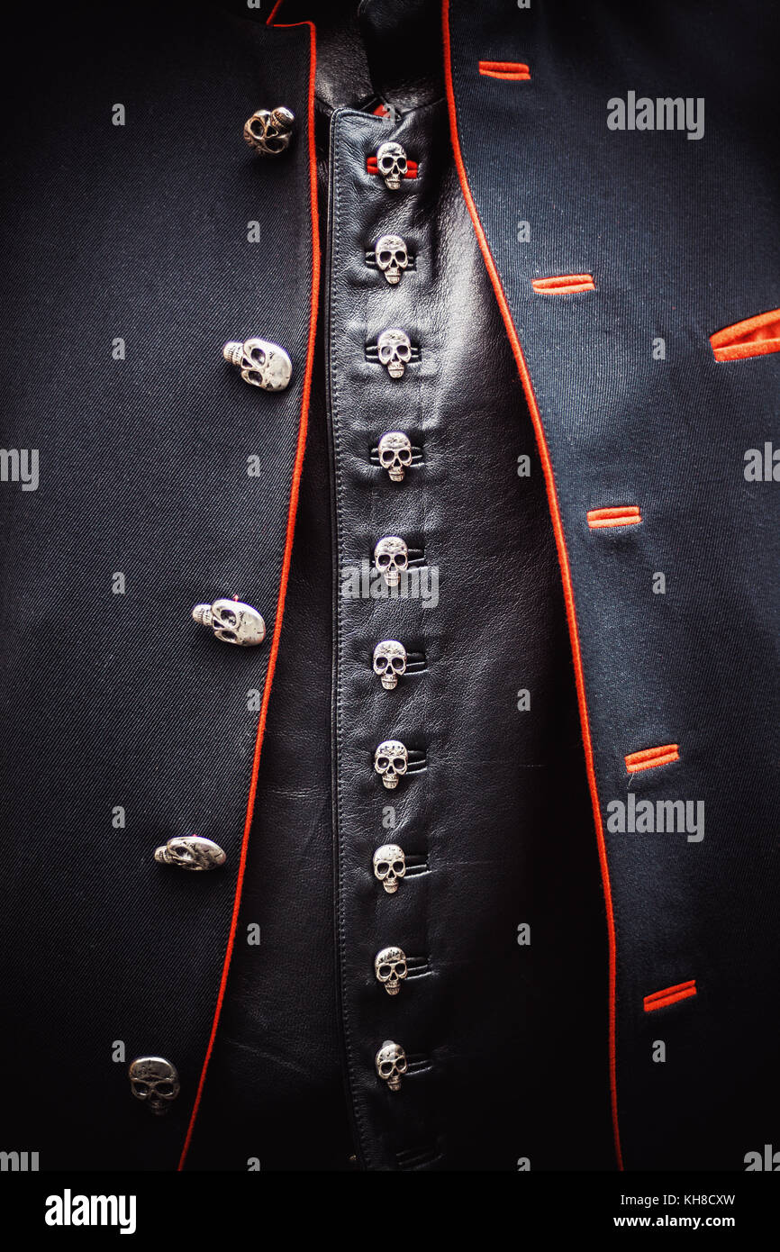 Closeup view on black vintage suit, jacket and vest with buttons in shape of small skulls. - Stock Image